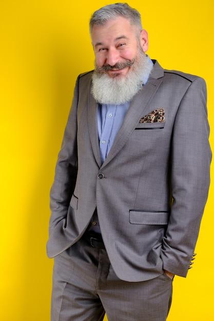 Lustiger bärtiger mann des studioporträts im grauen geschäftsanzug, der kamera, arbeitsberufslebensstil, gelben hintergrund sucht. Premium Fotos