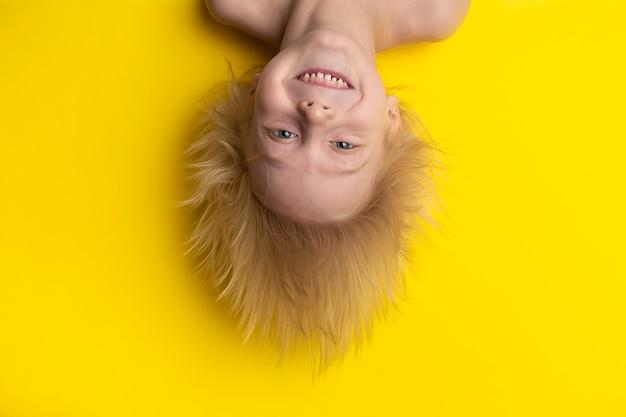 Lustiger blonder junge mit dem langen haar, das kopfüber hängt. fröhliches porträt des kindes auf gelbem raum Premium Fotos