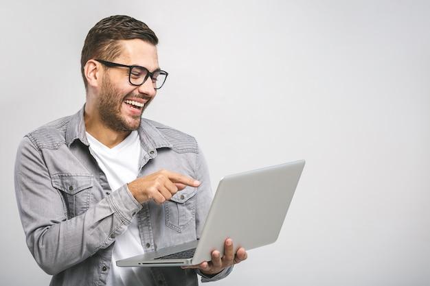 Lustiger junger hübscher mann im hemd, der laptop hält und lächelt, während er gegen weißen hintergrund steht. habe spaß. Premium Fotos