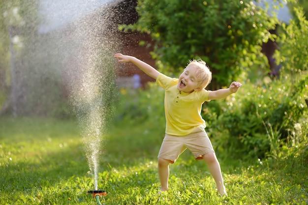 Lustiger kleiner junge, der mit gartenberieselungsanlage im sonnigen hinterhof spielt Premium Fotos
