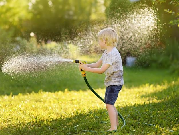 Lustiger kleiner junge, der mit gartenschlauch im sonnigen hinterhof spielt. vorschulkind, das spaß mit spray des wassers hat. Premium Fotos