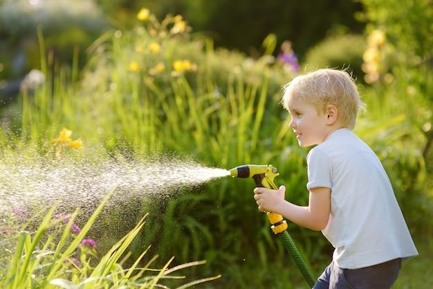 Lustiger kleiner junge, der mit gartenschlauch im sonnigen hinterhof spielt Premium Fotos