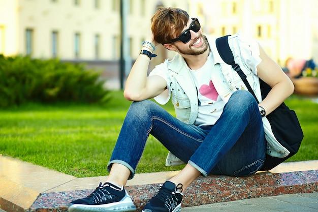 Lustiger lächelnder kerl des gutaussehenden mannes des hippies im stilvollen sommerstoff in der straße, die auf gras im park sitzt Kostenlose Fotos