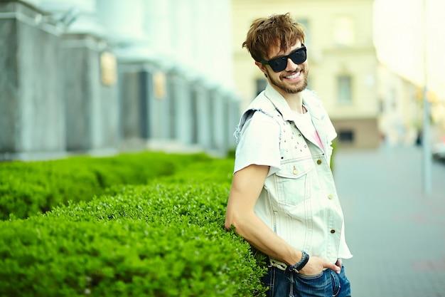 Lustiger lächelnder kerl des gutaussehenden mannes des hippies im stilvollen sommerstoff in der straße in der sonnenbrille Kostenlose Fotos