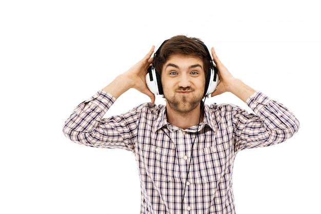 Lustiger mann genießen das hören von musik in kopfhörern Kostenlose Fotos