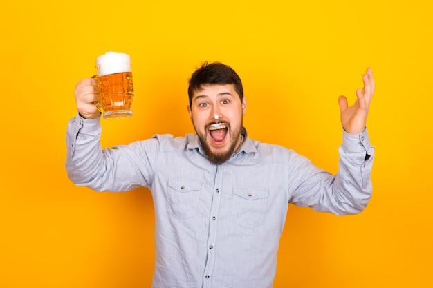 Lustiger mann mit einem glas bier und schaum auf seinem schnurrbart und nase auf einer gelben wand, partykonzept Premium Fotos