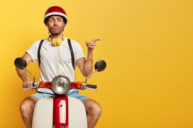 Lustiger schöner männlicher fahrer auf roller mit rotem helm Kostenlose Fotos