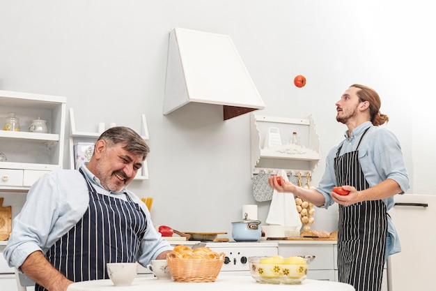 Lustiger sohn, der mit tomaten jongliert Kostenlose Fotos