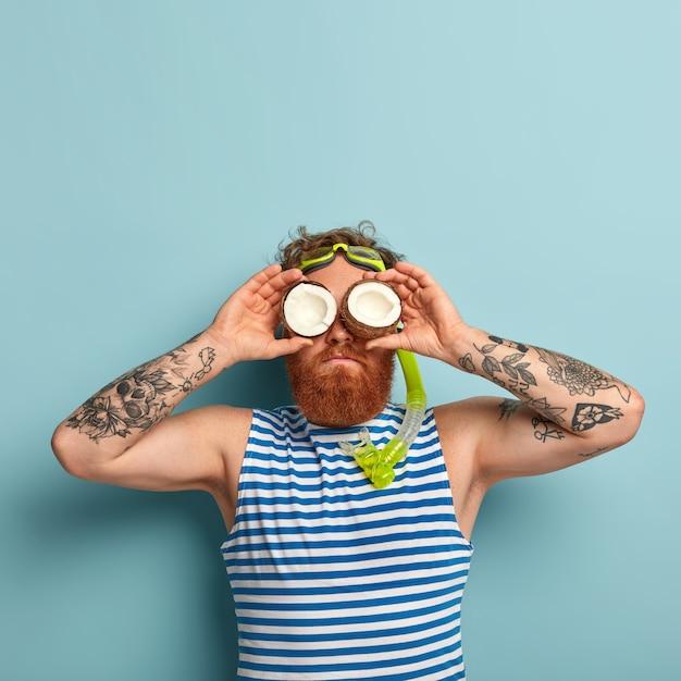 Lustiger verspielter bärtiger mann trägt schnorchelmaske, bereitet sich auf das tauchen unter wasser vor, hält zwei kokosnüsse auf augen Kostenlose Fotos