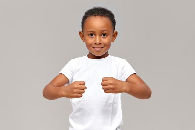 Lustiger zehnjähriger afrikanischer junge im weißen t-shirt, der geballte fäuste vor ihm hält, um stärke zu demonstrieren oder unsichtbare gegenstände zu halten Kostenlose Fotos