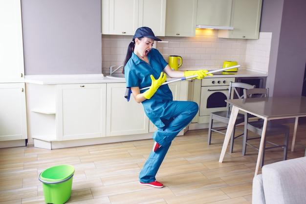 Lustiges arbeitskrafttanzen in der küche. sie gibt vor, auf der gitarre zu spielen Premium Fotos