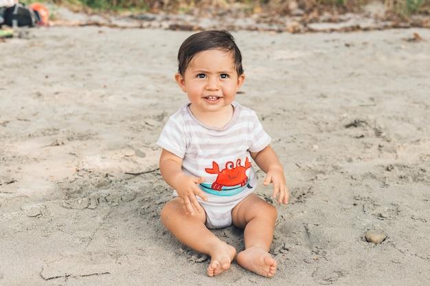Lustiges baby, das auf sandigem strand sitzt Kostenlose Fotos