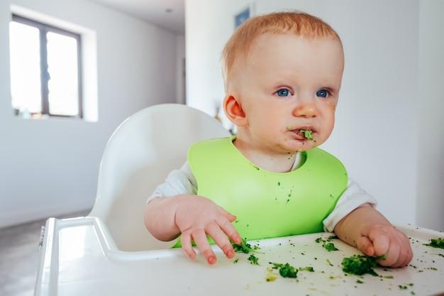 Lustiges baby, das weiches gekochtes gemüse selbst isst Kostenlose Fotos