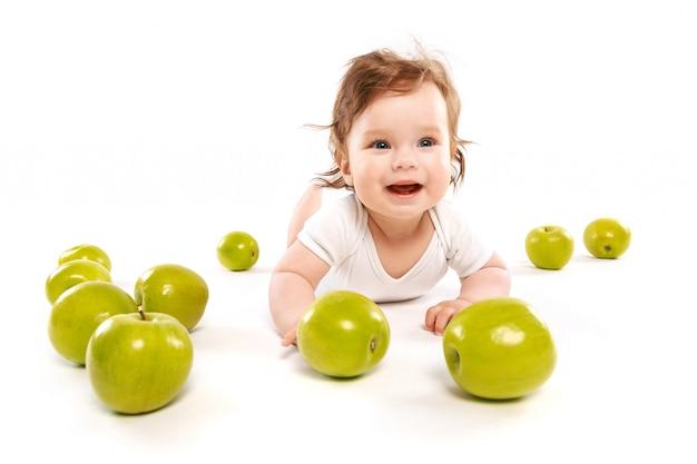 Lustiges baby, umgeben von grünen äpfeln Premium Fotos