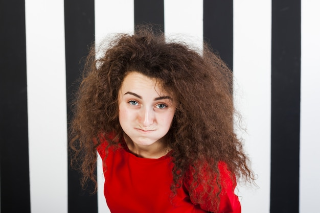 Lustiges brunettemädchenporträt auf gestreiftem hintergrund Kostenlose Fotos