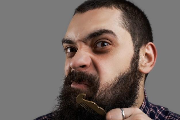 Lustiges gesicht des brutalen mannes, der seinen großen bart kämmt. friseurkonzept. Kostenlose Fotos