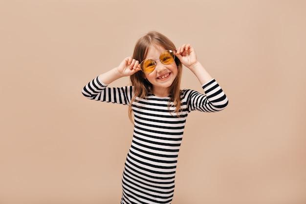 Lustiges glückliches 6 jahre altes mädchen im entkleideten kleid, das runde orange brille trägt, die weg mit charmantem lächeln über beigem hintergrund schaut Kostenlose Fotos