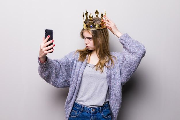 Lustiges junges mädchen der schönheit mit papiergeburtstagskrone auf stock, der selfie mit ihrem handy macht Kostenlose Fotos