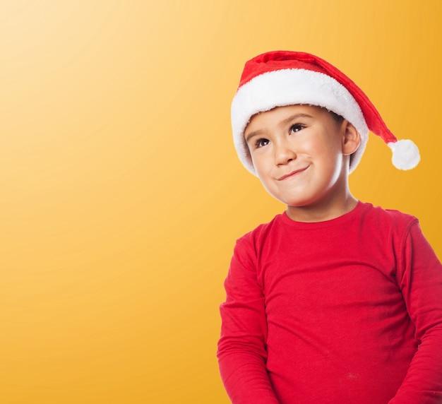 Lustiges kind mit weihnachtsmütze mit orangefarbenen hintergrund Kostenlose Fotos