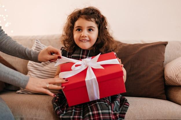 Lustiges kleines kind, das geburtstagsgeschenk hält. curly preteen mädchen mit geschenk, das auf sofa sitzt. Kostenlose Fotos