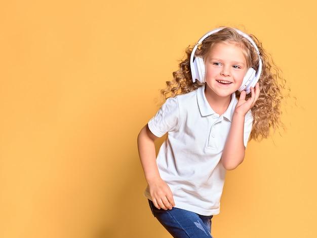 Lustiges kleines kindermädchen im weißen t-shirt lokalisiert auf gelbem raum. lifestyle-konzept für kinder. kopieren sie den speicherplatz. hören sie musik in kopfhörern und tanzen sie mit flatternden haaren Premium Fotos