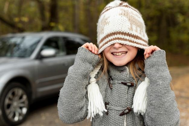 Lustiges kleines mädchen, das ihr gesicht mit winterhut bedeckt Kostenlose Fotos