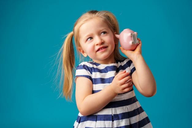 Lustiges kleines mädchen mit sparschwein-sparbüchsenporträt Premium Fotos