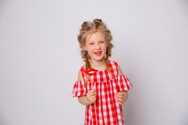 Lustiges lächelndes sommerkleid des kleinen mädchens auf weißem hintergrund. baby mit einem lippenzubehör auf einem stock. Premium Fotos