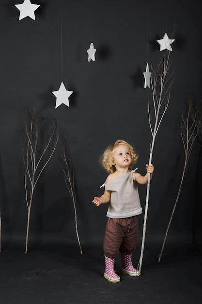 Lustiges lockiges mädchen auf einem grauen hintergrund mit bäumen Premium Fotos