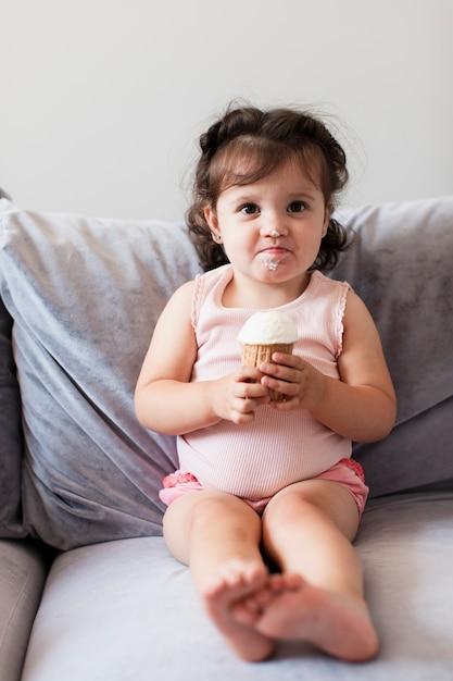 Lustiges mädchen, das eine eiscreme auf dem sofa isst Kostenlose Fotos