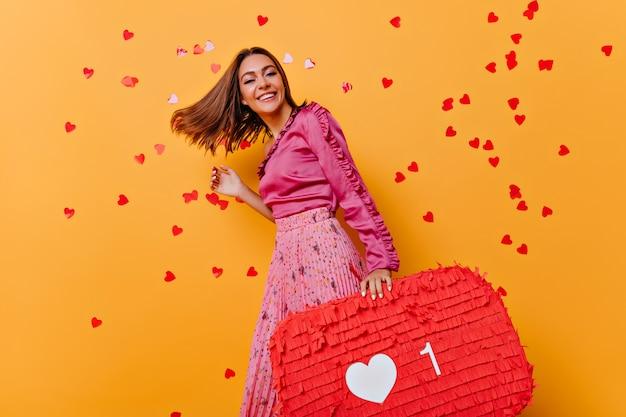 Lustiges mädchen im rosa blusentanzen. erstaunliches kaukasisches modell, das portraitshoot mit konfetti genießt. Kostenlose Fotos
