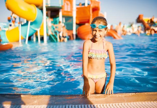 Lustiges mädchen in der blauen schutzbrille zum schwimmen steht in einem pool mit sauberem transparentem wasser, das in die kamera schaut und die warme sommersonne genießt Premium Fotos