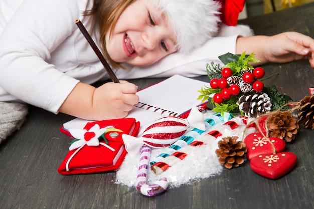 Lustiges mädchen in sankt-hut schreibt brief zu sankt nahe weihnachtsde Premium Fotos