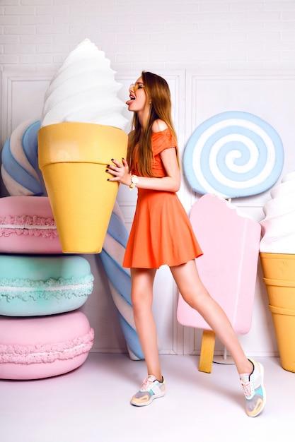 Lustiges modeporträt der hübschen blonden frau, die rieseneis hält und nahe große falsche süße, pastellfarben, schönes kleid, süßwarenladen aufwirft. Kostenlose Fotos