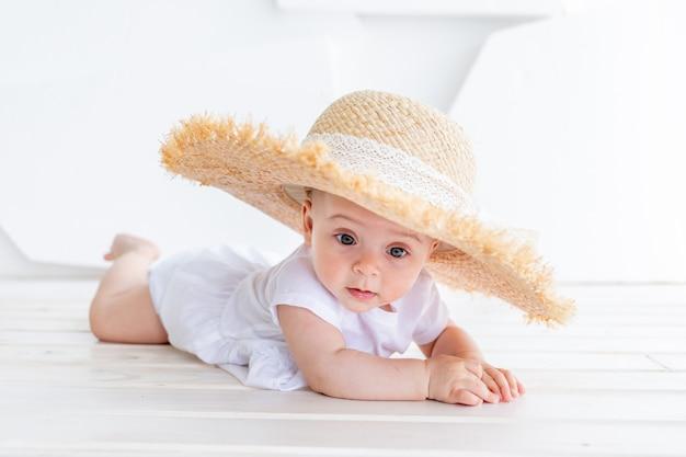 Lustiges niedliches kindermädchen 3-4 jahre alt, das strohhut mit weißem oberteil und jeansshorts hält Premium Fotos