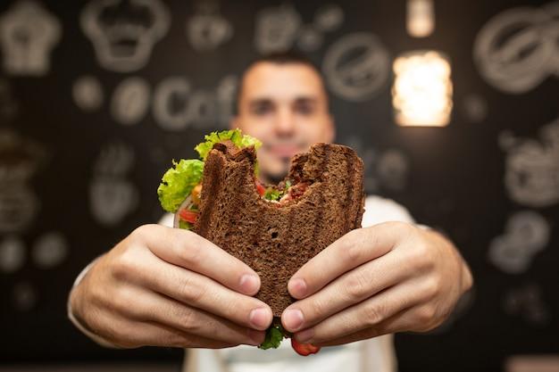 Lustiges unscharfes porträt der nahaufnahme des griffs des jungen mannes gebissenes sandwich durch seine zwei hände. Premium Fotos