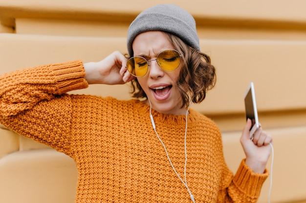 Lustiges weibliches modell mit kurzen lockigen haaren, die lieblingslied singen, während auf der straße mit smartphone stehen Kostenlose Fotos