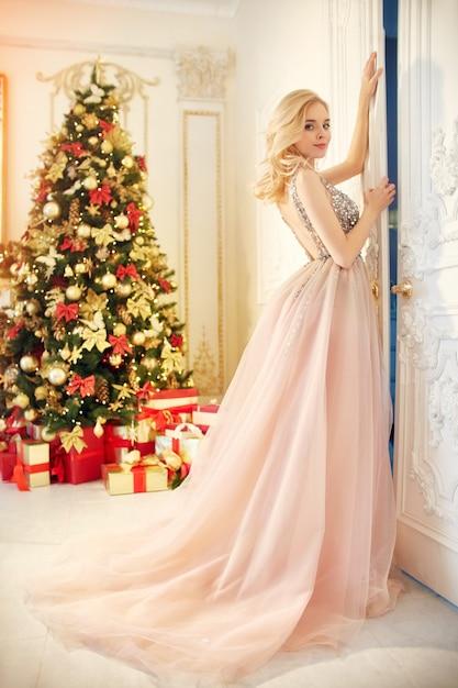 Luxuriöse blondine in einem abendkleid nahe einem weihnachtsbaum Premium Fotos