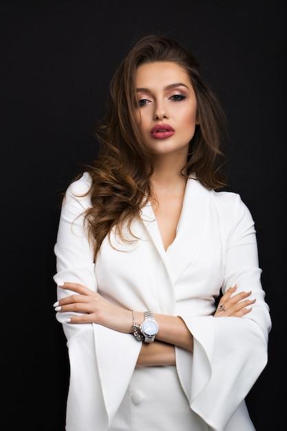 Luxuriöser brunette in einem weißen kleid auf einem schwarzen Premium Fotos