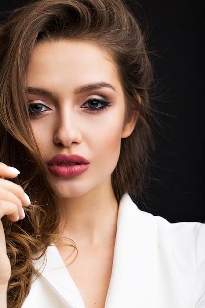 Luxuriöser brunette in einem weißen kleid auf schwarzem Premium Fotos