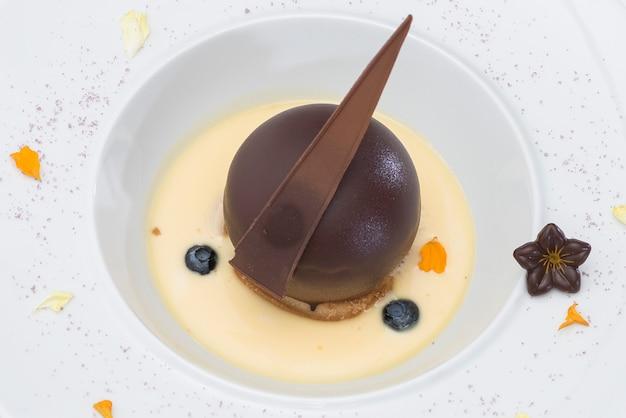 Luxuriöses dessert mit schokoladenkugel und vanillesauce, serviert auf einem keks, mit chocolade Premium Fotos