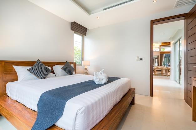 Luxus-innenausstattung im schlafzimmer der pool-villa mit gemütlichen kingsize-bett. hohe decke, h Premium Fotos