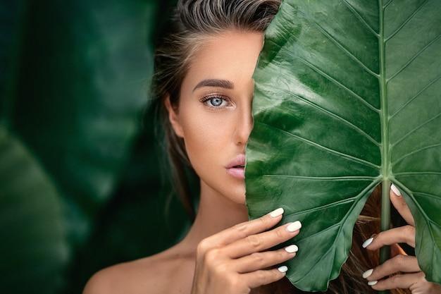 Luxusporträt einer schönen jungen frau mit natürlichem make-up hält ein großes grünes blatt auf unscharfem grün Premium Fotos