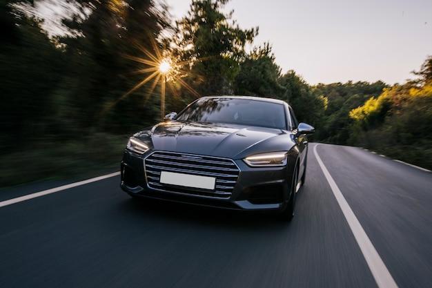 Luxussportwagen mit xenonlichtern. vorderansicht. fahren sie in den sonnenuntergang. Kostenlose Fotos