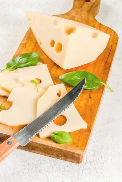 Maasdam-käse auf einem schneidebrett mit blättern des basilikums Premium Fotos