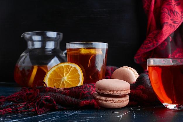 Macarons mit einem glas tee. Kostenlose Fotos