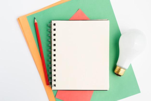 Machen sie briefpapier und weiße glühlampe über weißer oberfläche in handarbeit Kostenlose Fotos