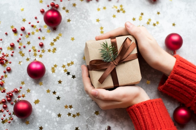Machen sie geschenk des braunen papiers mit den zweigen des weihnachtsbaums und der schnur in den händen eines mädchens mit roter strickjacke mit einer nackten maniküre in handarbeit. Premium Fotos