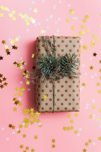 Machen sie geschenk mit schnur und kiefernniederlassung auf rosa pastell mit goldkonfettis in handarbeit. Premium Fotos