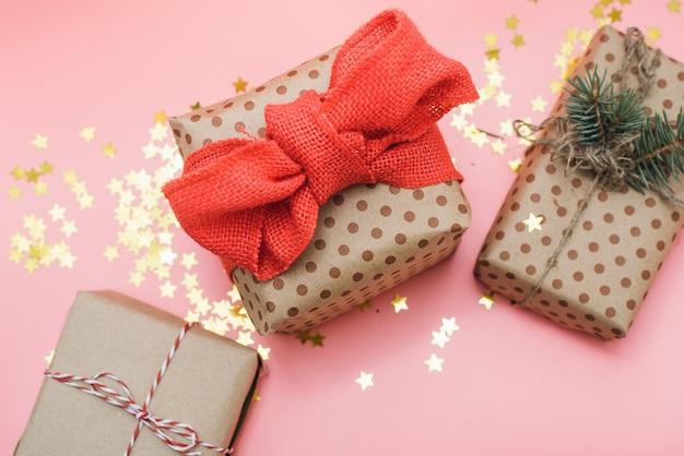 Machen sie geschenke mit rotem bogen auf rosa pastell mit goldkonfettis in handarbeit Premium Fotos